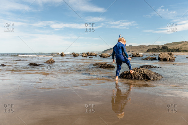 Young boy exploring back wearing snorkel on the coast of New Zealand