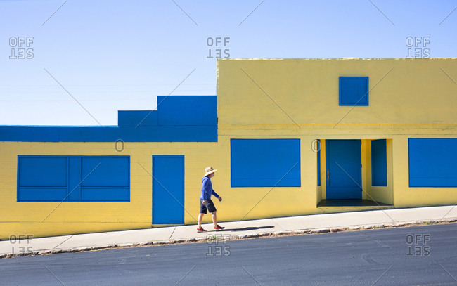 Man walking by yellow and blue abandoned building in Show Low, Arizona