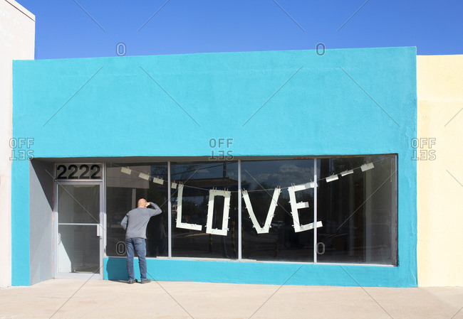 "Globe, Arizona, USA - October 2, 2019: Man looking into an abandoned store with ""love"" banner in window"