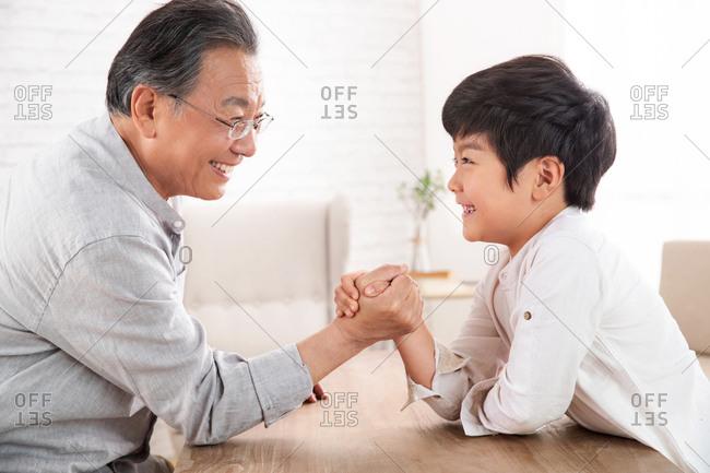 Grandpa and grandson arm-wrestling