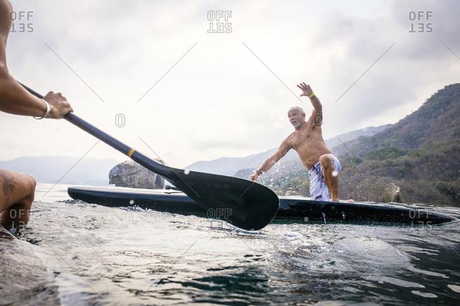 Mexico- Banderas Bay- Los Arcos National Marine Park- man falling from paddleboard