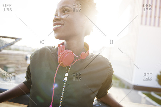 Smiling young woman with headphones at backlight