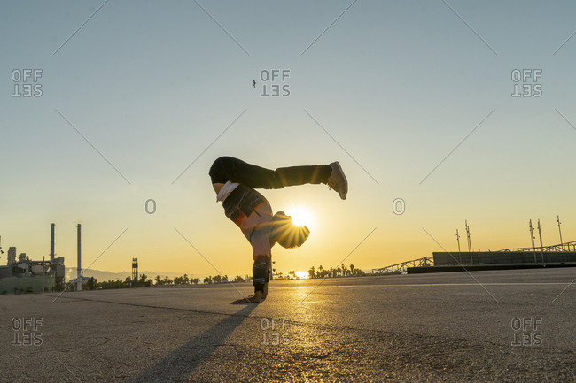 Acrobat doing handstand in the city at sunrise