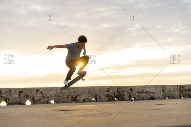 Young Chinese man skateboarding at sunrise near the beach