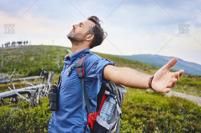 Man with closed eyes enjoying beautiful evening in mountains