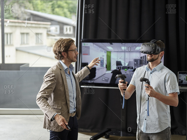 Man talking to colleague wearing VR glasses in front of screen