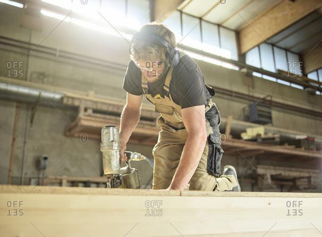 Carpenter fixing medium-density fiberboard with air nailer