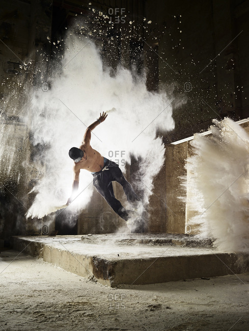 Man jumping in flour dust cloud during free running exercise
