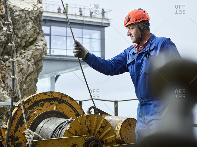 Germany- Bavaria- Garmisch-Partenkirchen- Zugspitze- installer working with rope pulley on goods cable lift