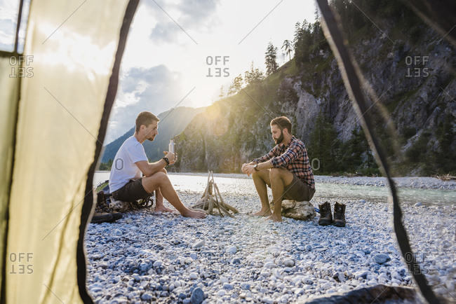Germany- Bavaria- two hikers camping on gravel bank in the evening
