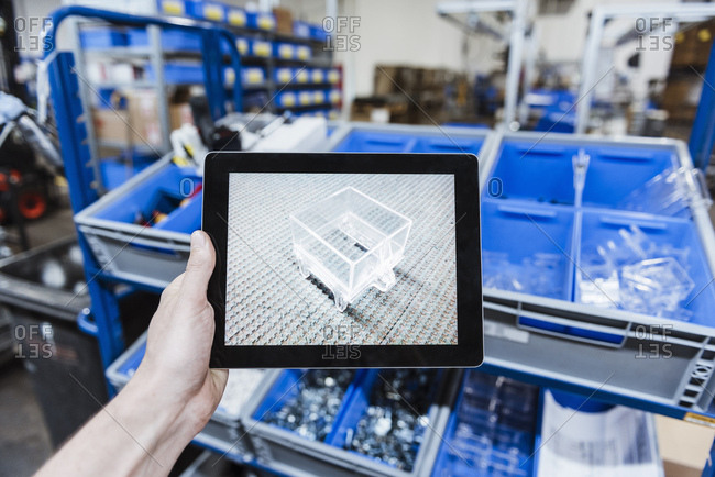 Hand holding digital tablet with image of a product