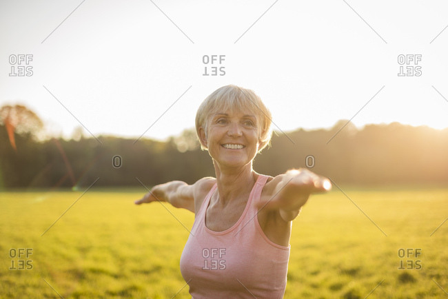 Portrait of smiling senior woman doing yoga on rural meadow at sunset