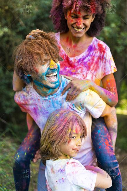 Family full of colorful powder paint- celebrating Holi- Festival of Colors