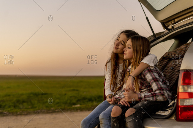 Two happy sisters sitting at opened tail watching sunset together