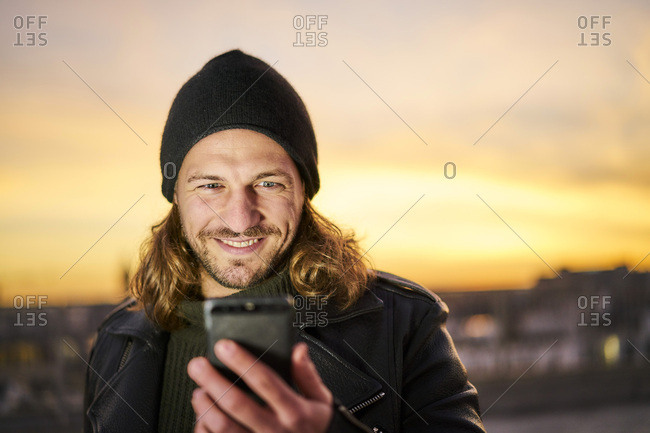 Portrait of bearded young man wearing wooly hat looking at mobile phone by sunset