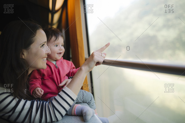 Happy mother and baby girl traveling by train looking out of window