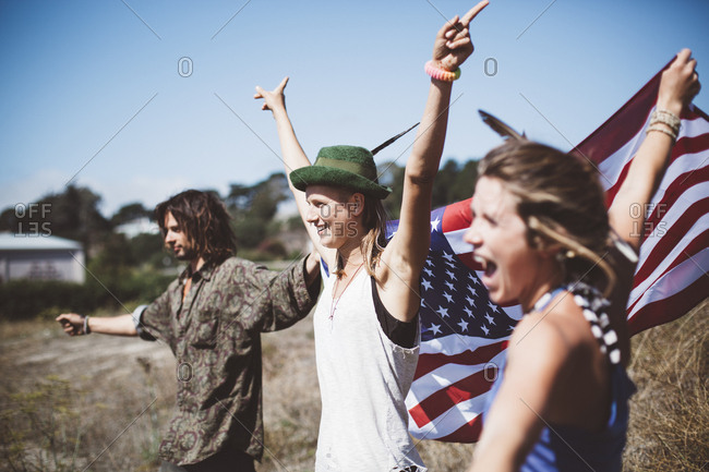 Three cheering hippies with US flag in the nature
