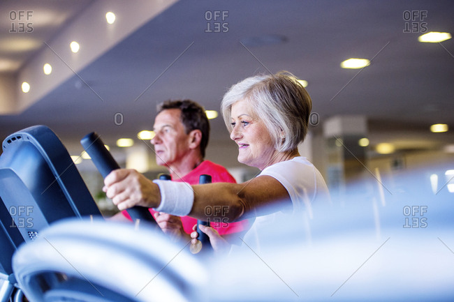 Senior man and mature woman on step machine in fitness gym