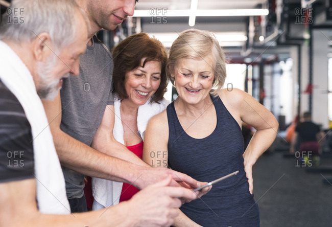 Group of fit seniors and personal trainer in gym looking at tablet