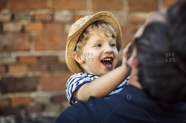Portrait of laughing toddler having fun with his father