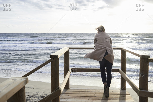 Spain- Menorca- back view of senior woman standing on boardwalk in winter looking at the sea