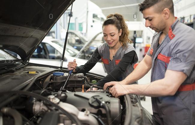 Mechanics working in workshop- repairing car