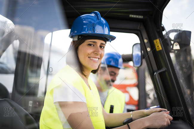 Female construction worker driving a forklift