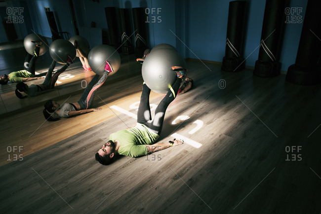 Man and woman exercising with fitness ball in gym