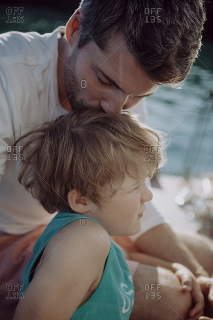 Father kissing son on a sailing boat