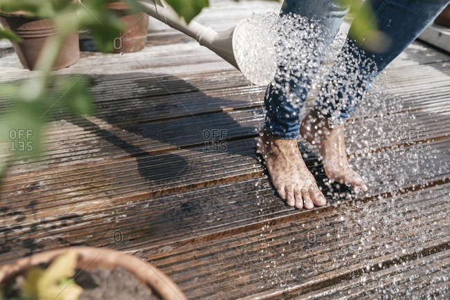 Woman with watering can pouring water over her feet