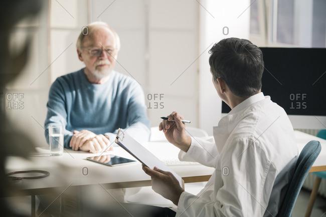 Doctor talking to senior patient in medical practice