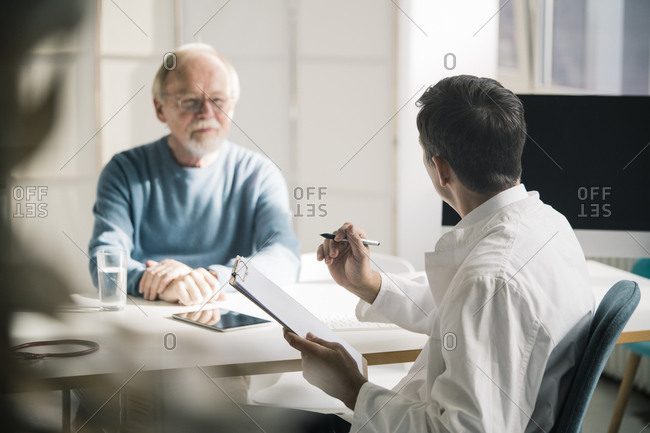 Doctor talking to senior patient in medical practice