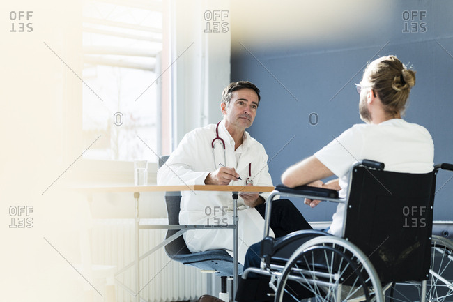 Doctor listening to patient in wheelchair in medical practice