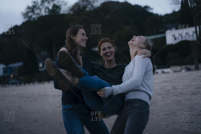 Germany- Hamburg- carefree mother with two teenage girls on the beach at Elbe shore in the evening