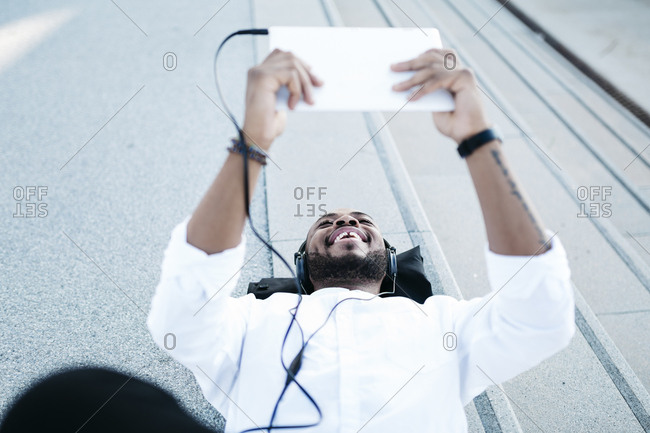 Happy man lying on the floor wearing headphones looking at tablet