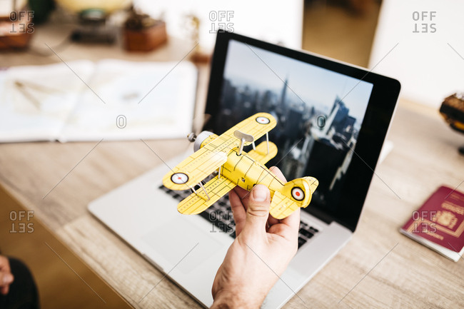 Man holding toy plane in front of laptop