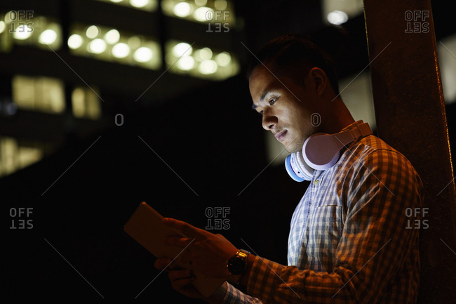Portrait of young man in the city using tablet at night