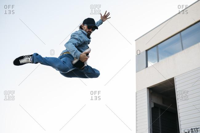 Trendy man in denim and cap doing jump