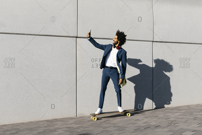 Young businessman riding skateboard along a wall taking a selfie