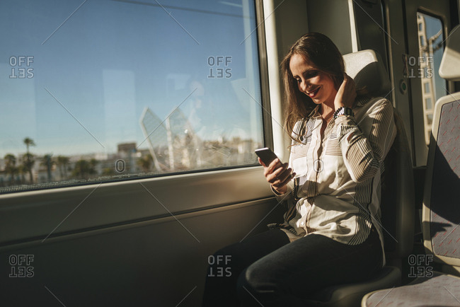 Smiling woman on a train looking at cell phone