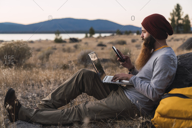 USA- North California- bearded young man using cell phone and laptop near Lassen Volcanic National Park