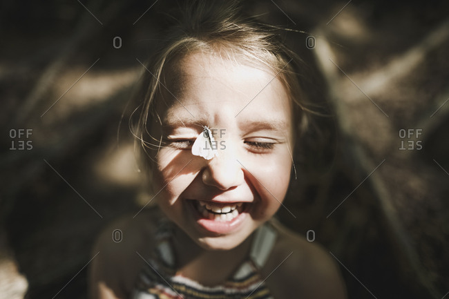 Portrait of laughing little girl with butterfly on her face