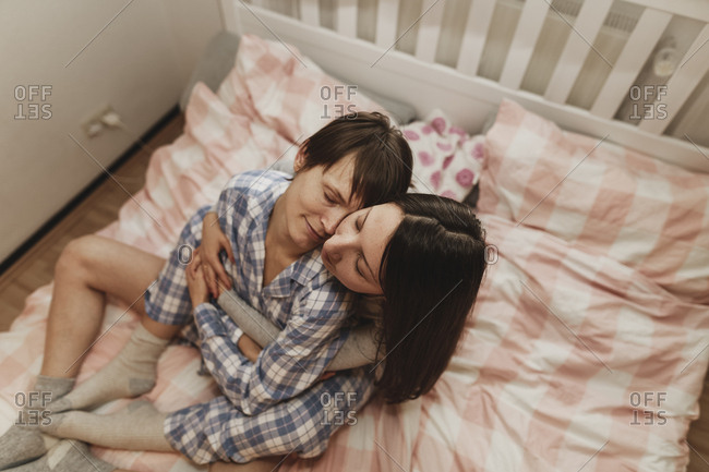 Lesbian couple hugging in bed
