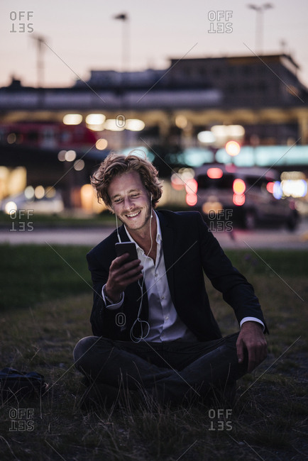 Smiling businessman sitting on meadow at dusk with cell phone and earphones