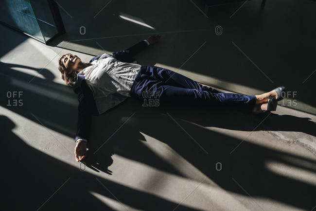 Businesswoman lying on floor in office