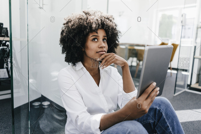 Young woman in office holding tablet thinking