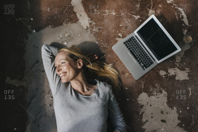 Smiling woman lying on the floor next to laptop
