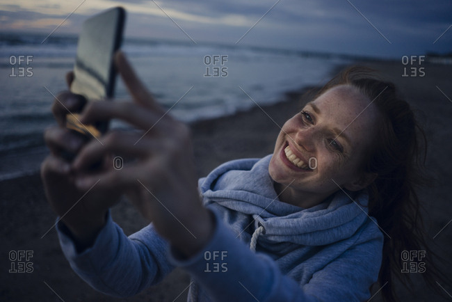 Woman using smartphone on the beach at sunset