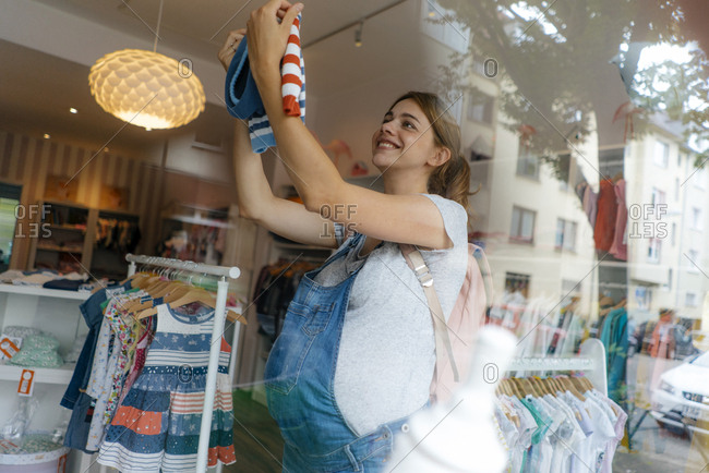 Smiling pregnant woman shopping for baby clothing in a boutique
