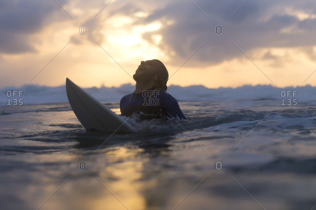 Indonesia- Bali- surfer in the ocean at sunrise